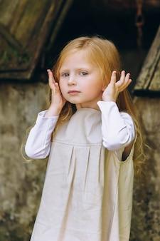 Bella bambina con una brocca e un secchio vicino al pozzo sullo sfondo di alberi ed erbe