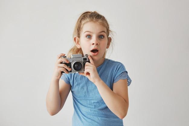 Bella bambina divertente con capelli biondi e gli occhi azzurri che tengono la macchina fotografica della foto in mano, guardando dritto con espressione spaventata.
