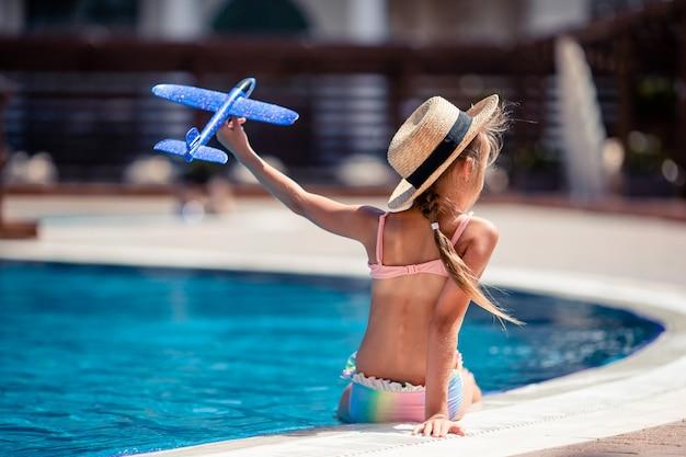 Bella bambina divertirsi vicino a una piscina all'aperto
