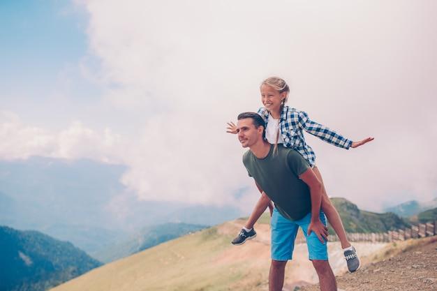 Bella bambina e giovane padre in montagne sullo sfondo della nebbia