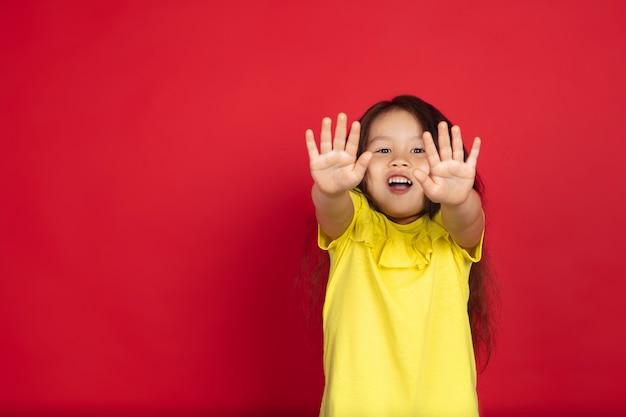 Bella bambina emotiva isolata su spazio rosso. ritratto a mezza lunghezza del bambino felice che mostra un gesto e che indica in su. concetto di espressione facciale, emozioni umane, infanzia.