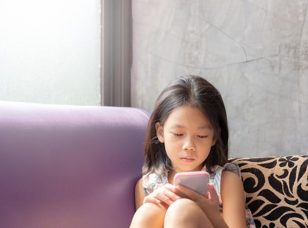 Bella bambina felice con smart phone che si siede sul divano