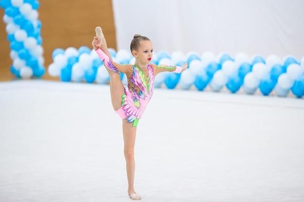 Bella bambina ginnasta attiva con le sue prestazioni sul tappeto