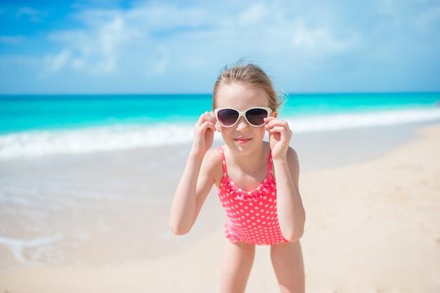 Bella bambina in abito in spiaggia divertendosi.