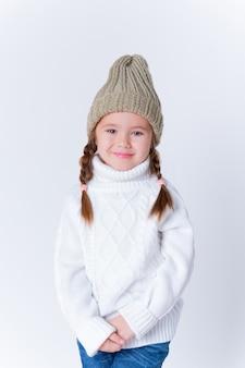 Bella bambina in maglione e cappello lavorato a maglia