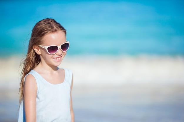 Bella bambina in occhiali da sole in spiaggia divertendosi. la ragazza divertente gode delle vacanze estive.
