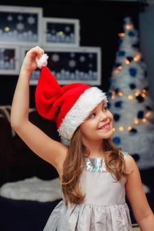 Bella bambina in un cappello di natale. il concetto di capodanno e buon natale