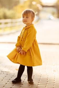 Bella bambina in un vestito giallo divertendosi e giocando nella sosta di autunno il giorno pieno di sole