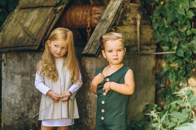 Bella bambina in una camicia bianca con un ragazzo in una combinazione verde vicino al pozzo
