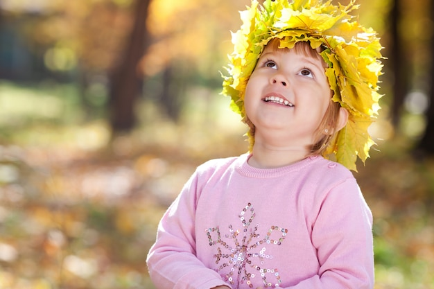 Bella bambina in una corona di foglie di acero nella foresta di autunno