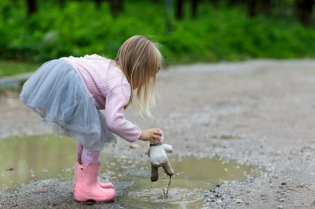Bella bambina in una gonna tutu battuta un orsacchiotto in una pozzanghera sulla strada