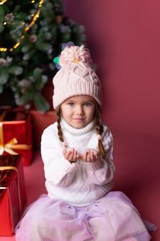 Bella bambina nel cappello che gioca con la neve vicino ai regali e all'albero di natale