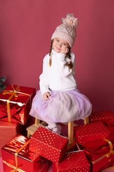 Bella bambina nel cappello che si siede vicino ai regali e all'albero di natale
