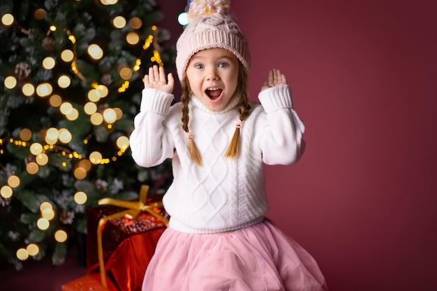 Bella bambina nel cappello sorprendente vicino a regali e albero di natale