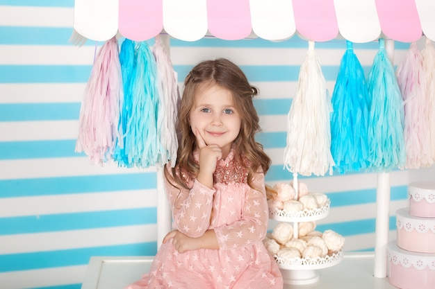 Bella bambina seduta sul tavolo con caramelle. la barra del compleanno di candy. ritratto di un primo piano del viso del bambino.