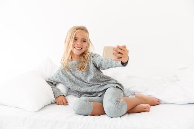 Bella bambina sorridente che prende selfie sullo smartphone mentre trovandosi nel letto molle