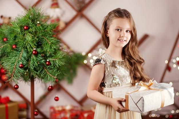 Bella bambina sorridente che tiene un contenitore di regalo di natale. celebrazione di natale e capodanno.