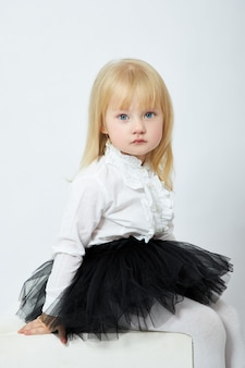 Bella bambina su un muro bianco