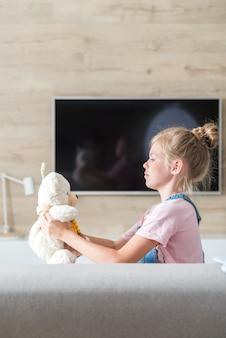 Bella bambina sul divano che abbraccia orsacchiotto, il concetto di un'infanzia felice, gioco in famiglia,