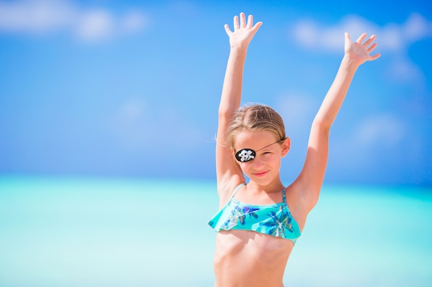 Bella bambina sulla spiaggia divertendosi. la ragazza felice gode del fondo di vacanze estive l'acqua del turchese e del cielo blu nel mare sull'isola dei caraibi