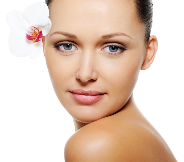 Bella bella donna con pelle chiara e fiore vicino ai suoi occhi
