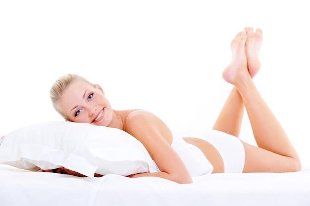 Bella bella donna in lingerie bianca sdraiata sul cuscino bianco
