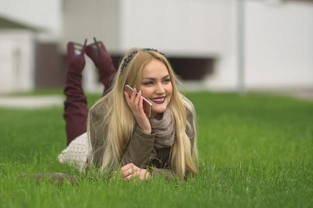 Bella bionda positiva in vestiti alla moda parlando con qualcuno al telefono sdraiato sul prato verde nel parco su sfondo di edificio sfocato