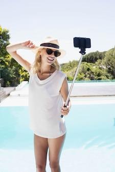 Bella bionda prendendo selfie in piscina