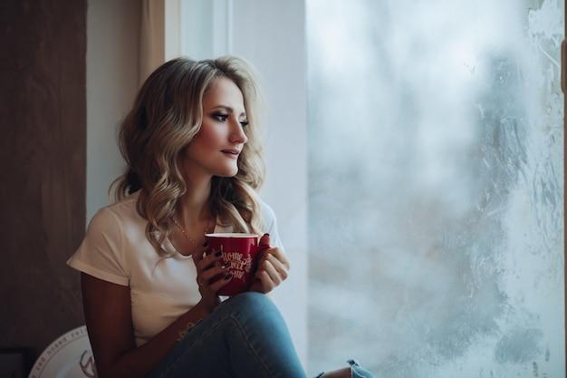 Bella bionda seduta sul davanzale della finestra con la tazza
