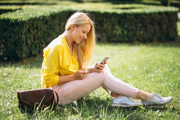 Bella bionda seduta sull'erba e lavorando sul portatile