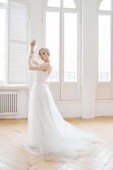 Bella bionda snella sotto il sole della sera in un lungo abito bianco vicino a una grande finestra. capelli e trucco perfetti per la sposa, una nuova collezione di abiti da sposa