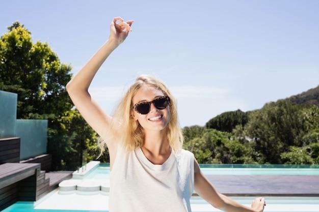 Bella bionda sorridendo alla telecamera a bordo piscina