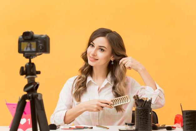 Bella blogger che spazzola i capelli sulla macchina fotografica