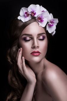Bella bruna con i capelli lunghi e corona di fiori