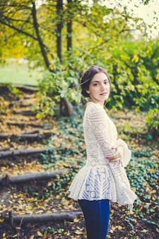 Bella bruna con le trecce intorno alla testa in un'elegante camicetta a maniche lunghe in pizzo bianco vintage in un parco in autunno