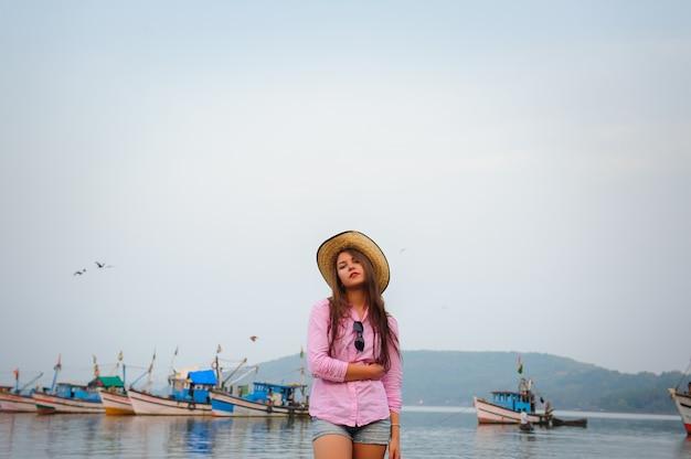 Bella bruna dai capelli lunghi si erge sullo sfondo della baia e barche da pesca