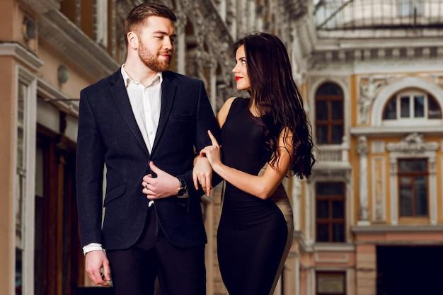 Bella bruna elegante con suo marito che cammina per le strade della città della birra inglese. godendo del tempo lì, indossando un abito classico nero e un lungo abito da cocktail.