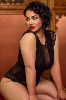 Bella bruna giovane brillante con grandi forme in lingerie