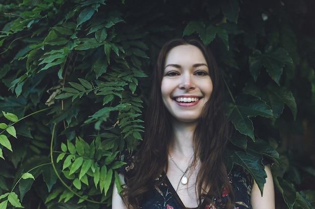 Bella bruna in un fogliame verde, sorridente