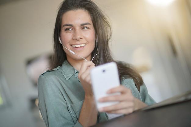 Bella bruna parlando sul cellulare con le cuffie a casa