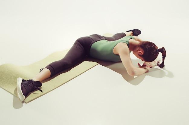 Bella bruna sottile facendo alcuni esercizi di stretching in palestra