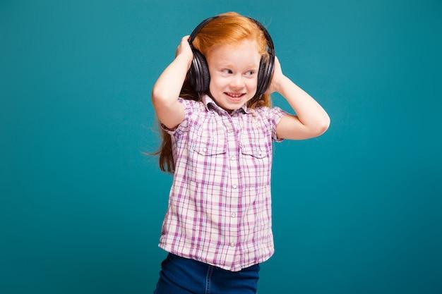 Bella, carina bambina in camicia a scacchi e auricolari con lunghi capelli rossi ascolta musik