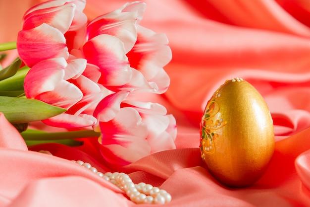 Bella carta di pasqua, sfondo con fiori e uova d'oro