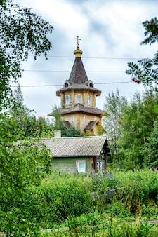 Bella chiesa in legno nel paesaggio. verticale.