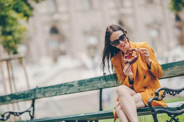Bella ciambellina salata della tenuta della giovane donna e rilassamento nel parco
