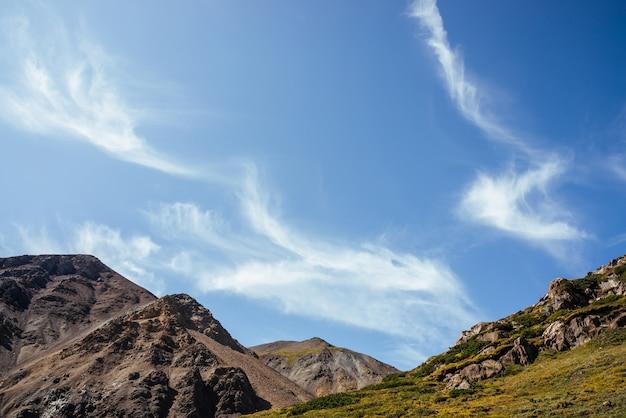 Bella cirri nel cielo blu sopra le rocce alla luce del sole.