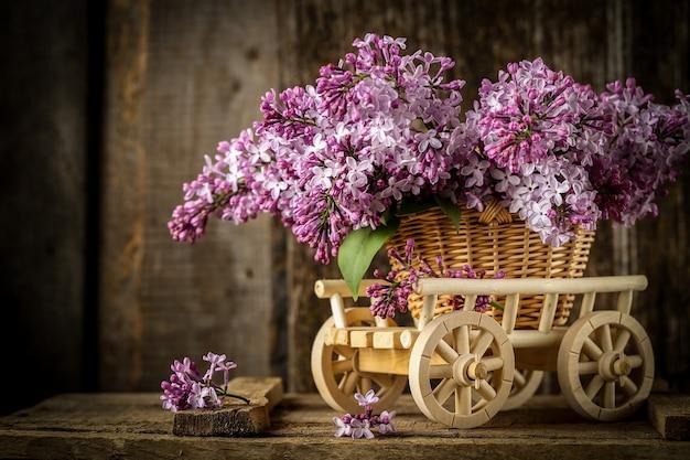 Bella composizione con bouquet di lillà in un cesto di vimini