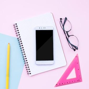 Bella composizione desktop con telefono, notebook, occhiali su sfondo rosa
