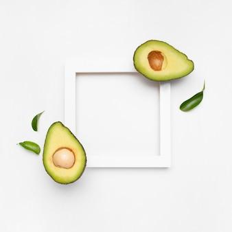 Bella composizione di avocado sulla superficie bianca con una cornice per il testo