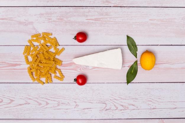 Bella composizione di pasta fusilli cruda; pomodori; formaggio; foglie di alloro e limone su fondo in legno